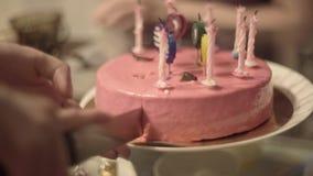 Torta del corte de la mano con las velas en la tabla, cierre para arriba almacen de metraje de vídeo