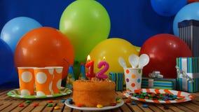 Torta del cumpleaños 12 en la tabla de madera rústica con el fondo de los globos coloridos, regalos, tazas plásticas, placa plást foto de archivo