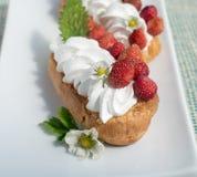Torta del Eclair con las fresas fotografía de archivo