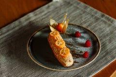 Torta del Eclair en una placa adornada con la fruta c?trica foto de archivo libre de regalías