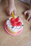 Torta del giocattolo di taglio della mano del bambino Fotografia Stock