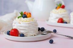 Torta del merengue, de Pavlova con las fresas, arándanos y menta imagenes de archivo