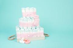 Torta del pañal con los patos de goma y los calcetines rosados en un fondo azul Fotografía de archivo libre de regalías