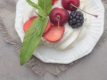torta del pavlova de los merengues con la cereza fresca, zarzamora, fresa en el fondo concreto, niebla suave fotos de archivo