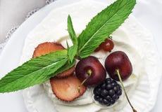 torta del pavlova de los merengues con la cereza fresca, zarzamora, fresa en fondo concreto imagenes de archivo
