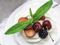 torta del pavlova de los merengues con la cereza fresca, zarzamora, fresa en fondo concreto fotos de archivo libres de regalías