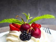 torta del pavlova de los merengues con la cereza fresca, zarzamora, fresa en fondo concreto fotos de archivo
