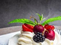torta del pavlova de los merengues con la cereza fresca, zarzamora, fresa en fondo concreto fotografía de archivo libre de regalías