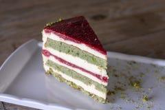 Torta del pistacho y de la baya en la placa blanca imagen de archivo libre de regalías