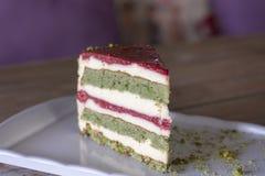 Torta del pistacho y de la baya en la placa blanca foto de archivo