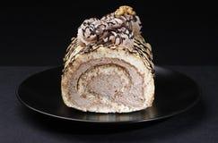 Torta del rollo dulce en fondo negro Fotos de archivo