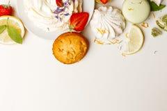 Torta delicada con los dulces y las fresas en una tabla blanca foto de archivo