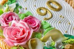 Torta deliciosa con las rosas, el lirio, las hojas y los cuadros 90 años en cierre de madera azul claro de la tabla para arriba c Fotografía de archivo libre de regalías