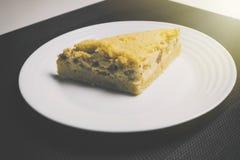 Torta della pesca su fondo in bianco e nero con luce solare dal lato Torta gialla della pesca sulla tavola in cucina Torta della  Fotografia Stock Libera da Diritti