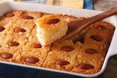 Torta di Basbousa con le mandorle macro in un piatto di cottura orizzontale Immagini Stock Libere da Diritti