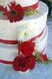 Torta di cerimonia nuziale con le bande ed i fiori rossi Fotografia Stock