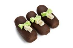 Torta di cioccolato tre con le rosette isolate Immagini Stock