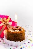Torta di compleanno con la candela e un regalo su un fondo bianco Fotografia Stock
