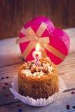 Torta di compleanno con la candela e un regalo sui vecchi precedenti di legno Immagini Stock