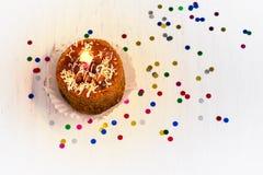 Torta di compleanno con la candela su un fondo bianco, vista superiore Immagine Stock