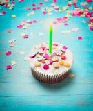 Torta di compleanno con la candela verde e coriandoli rosa sul fondo di legno elegante misero del blu di turchese Immagini Stock