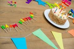 Torta di compleanno e decorazioni sulla Tabella Immagini Stock