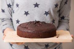 Torta di compleanno fresca casalinga del cioccolato nelle mani di una donna Un dolce piacevole per un partito Fondo grigio con le Fotografia Stock