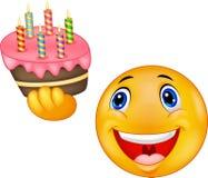 Torta di compleanno sorridente della tenuta dell'emoticon Immagini Stock