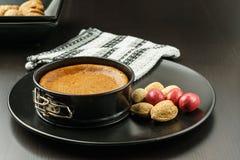 Torta di formaggio casalinga del cioccolato in piccola pentola dello springform sulla banda nera con i dadi sulla tavola Fotografia Stock