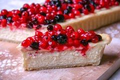Torta di formaggio del dessert con i redberries ed i mirtilli sulla polvere dello zucchero e del bordo di legno Fine in su Fotografia Stock
