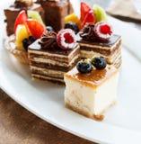 Torta di formaggio della vaniglia con il mirtillo Insieme di mini dolci in assortimento sul piatto bianco Il pranzo di cerimonia  Fotografia Stock