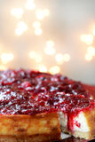 Torta di formaggio della vaniglia del mirtillo rosso con le luci su fondo Immagini Stock Libere da Diritti