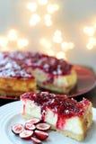 Torta di formaggio della vaniglia del mirtillo rosso con le luci su fondo Immagini Stock