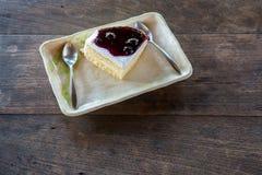 Torta di formaggio squisita del mirtillo Fette blu del dolce della bacca sul piatto di legno immagini stock libere da diritti