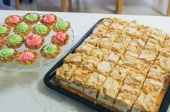 Torta di formaggio su un piatto e sui muffin, bigné decorati fotografia stock
