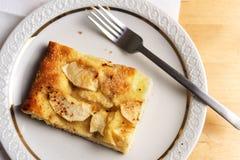 Torta di mele al forno fresca su un piatto bianco su una tavola di legno luminosa Immagini Stock Libere da Diritti