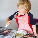 Torta di mele d'aiuto e bollente del piccolo bambino adorabile '' in ki domestico di s Fotografie Stock
