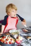 Torta di mele d'aiuto e bollente del piccolo bambino adorabile '' in ki domestico di s Fotografia Stock Libera da Diritti