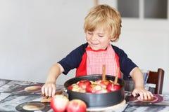 Torta di mele d'aiuto e bollente del ragazzino adorabile '' nel kitc domestico di s Fotografie Stock