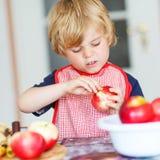 Torta di mele d'aiuto e bollente del ragazzino adorabile '' nel kitc domestico di s Fotografia Stock Libera da Diritti