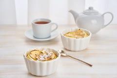 Torta di mele e tazza di tè sulla tavola di legno bianca in cucina Dessert delicato della cagliata con le mele, i fiocchi della m fotografia stock