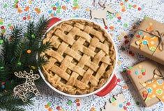 Torta di mele, regali di natale e decorazioni su fondo leggero Immagine Stock