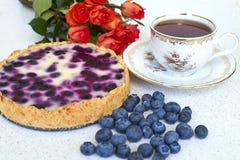 Torta di mirtillo, tazza di tè, mucchio dei mirtilli e rose rosse su un fondo bianco - alimento di natura morta Fotografia Stock