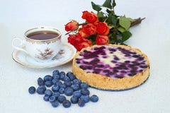 Torta di mirtillo, tazza di tè, mucchio dei mirtilli e rose rosse su un fondo bianco - alimento di natura morta Immagini Stock