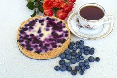 Torta di mirtillo, tazza di tè, mucchio dei mirtilli e rose rosse su un fondo bianco - direttamente sopra Fotografia Stock Libera da Diritti