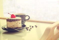 Torta dulce con una cereza y una taza de café Fotografía de archivo libre de regalías