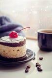 Torta dulce con una cereza y una taza de café Imagen de archivo libre de regalías