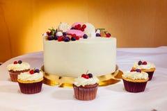 Torta e queques deliciosos bonitos do fruto na tabela doce Imagens de Stock