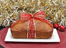 Torta entera del pan envuelta en una cinta del rojo y del oro Imágenes de archivo libres de regalías