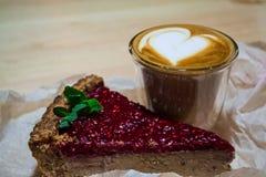 Torta fresca da framboesa da parte com cappuccino no vidro transparente com coração Arte do Latte Café fresco e bom dia na cafeta fotografia de stock royalty free